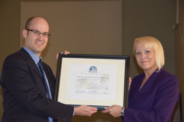 Alberta Historical Resources Foundation Executive Director Matthew Wangler presents the Alberta Main Street Program Membership to Angie McDow, President of the Old Strathcona Foundation.