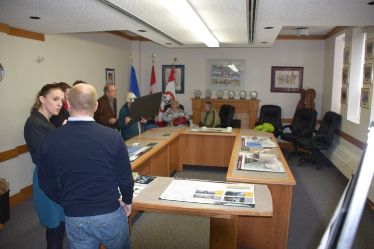 Image of people attending the open house in Raymond discussing the context paper.