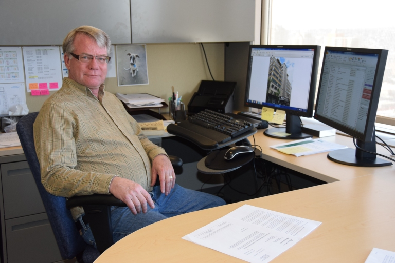 photograph of Larry Pearson, Director of the Historic Places Stewardship Section, at his desk.