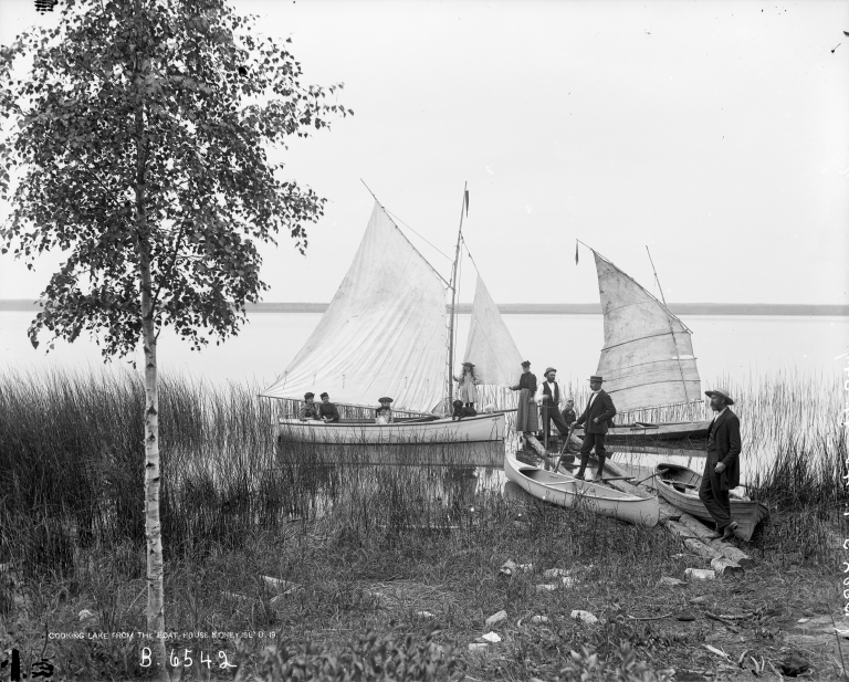 Koney Island Club member showing off their floatilla: The gaff-rigged sloop Mudhen, along with a row boat and two canoes, one with a small sail as was popular at the time. (Courtesy of the Provincial Archives of Alberta, B.6542.)