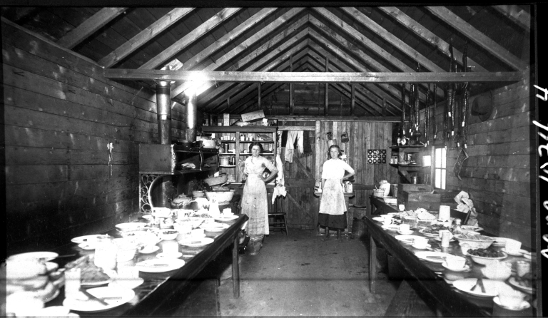Two women stand in a cookhouse at Newcastle Mine in Drumheller Valley, ca. 1912; Newcastle was one of the first mine operations in Drumheller Valley to establish a cookhouse, which fed up to 100 miners three times a day. Source: Courtesy of Atlas Coal Mine National Historic Site