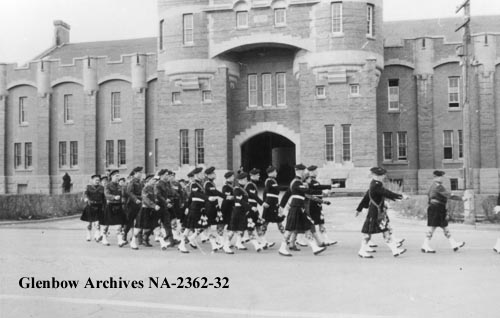 Calgary Highlanders pipe band parading by Mewata Armoury, Calgary, date unknown. (Glenbow Archives, NA-2362-32).