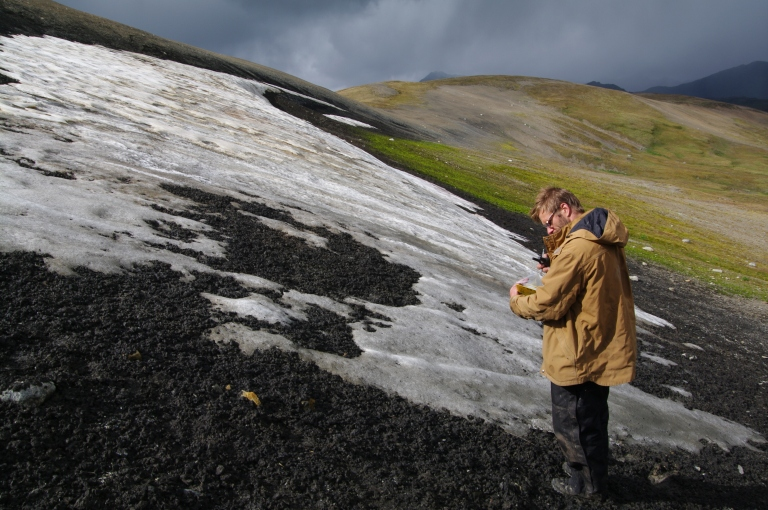 An archaeologist surveying a melting ice patch for artifacts (courtesy of Mike Donnelly).