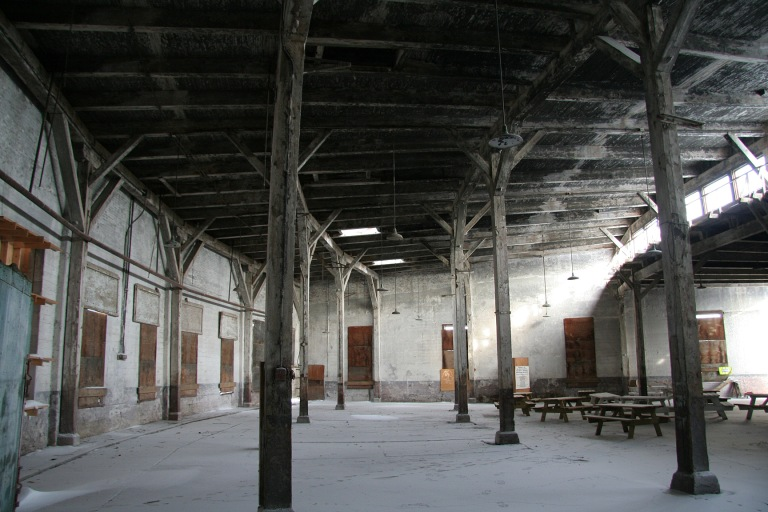 Interior of the Canadian Northern Railway Roundhouse, December 2013. The fan-shape of the building is evident in the curvature of the rear wall (to the left), the clerestory windows (at the right) and the arrangement of the ceiling supports and beams. Alberta Culture and Tourism, Government of Alberta.