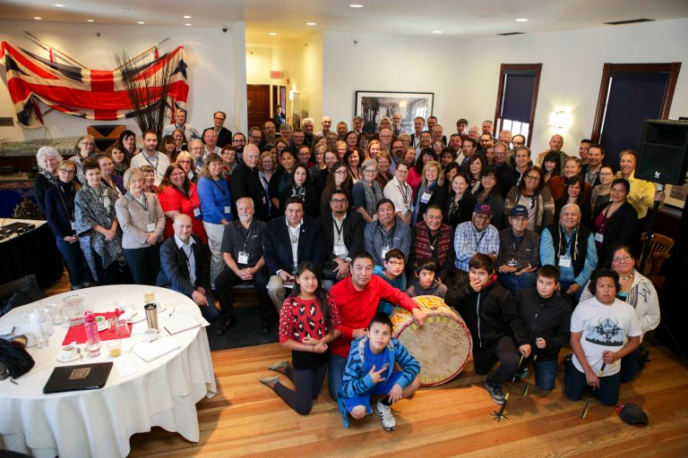 Participants of Moh-Kins-Tsis: Calgary Indigenous Heritage Roundtable pose for a group photo with the presenters and the Crowfoot Young Warriors. Photo credit: Pinpoint Photography, courtesy of the National Trust for Canada.
