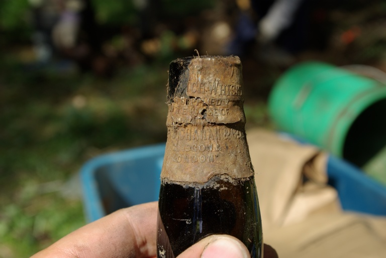 A liquor bottle with the label still on it was found at one of the private houses. The label indicates that the product was imported from the U.K. (Photo Credit: Lifeways of Canada Ltd.)