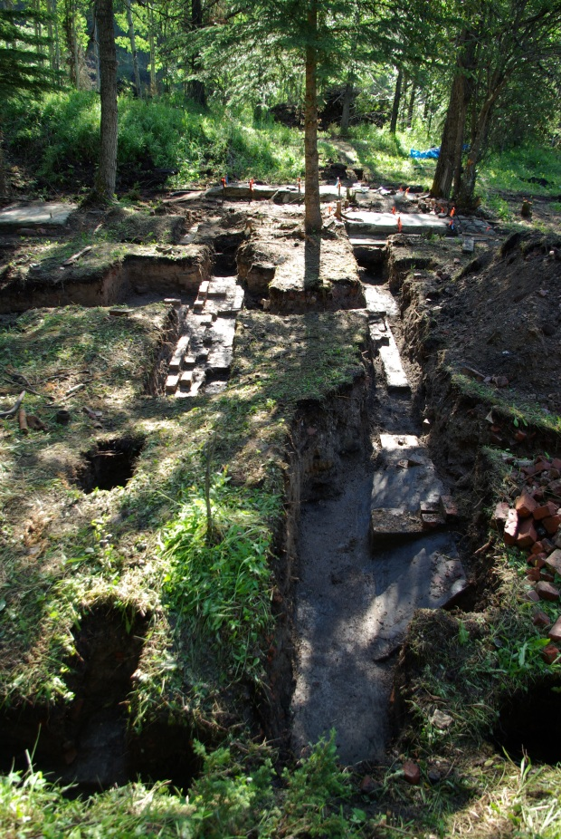 Archaeological excavation at the boiler house uncovered cement floors and platforms and brick walls, 2010. (Photo Credit: Lifeways of Canada Ltd.)
