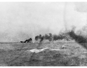 HMS Indefatigable slips below the surface, May 31, 1916. The ship took a shell behind one of her turrets, causing a massive explosion. Only two of her 1,019 crew survived. Of the killed was Lieutenant Engineer Stanley de Quetteville, RCN, the only confirmed Canadian casualty of the battle.