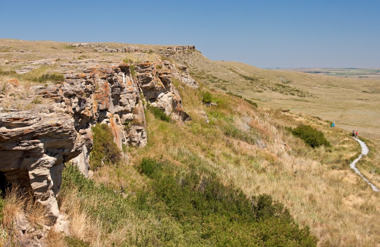 Figure 1. The sandstone cliffs at Head-Smashed-In are much shorter than in pre-contact times. Archaeologists have excavated through over 8 m of sediment and bone at the base of the cliff to reach the oldest layers of pre-contact hunting at Head-Smashed-In. Image courtesy of Alberta Culture and Tourism.