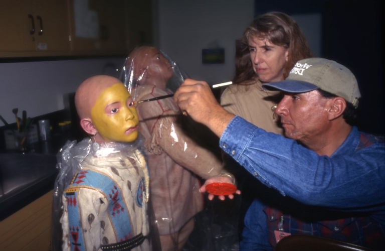 Allan painting a mannequin with the face paint for the weasel tail shirt for a Blackfoot display in the Royal Alberta Museum's former Gallery of Aboriginal Culture, 1997. Allan had the transferred rights to the face paint design as a weasel tail suit owner. (Photo Credit: Royal Alberta Museum)