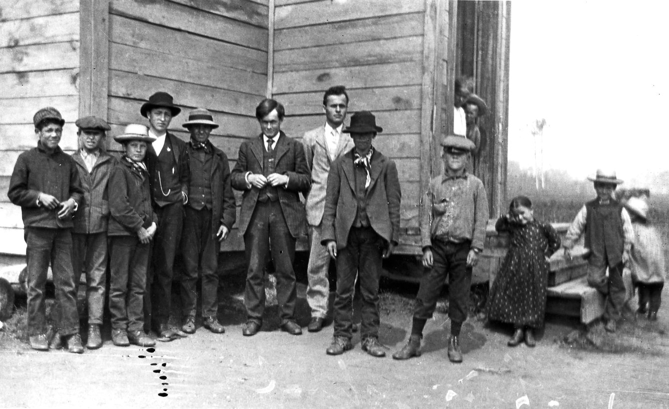 Students at Victoria School, circa 1910: Left to right Frank Whitford, Fred Kuzemsky, unidentified, Wasyl Kotyk, Wayne Kozub or Esepenko, teacher Mr. Rowbottom, Demetrius Ponich, Metro Starchuk, David Thompson, Elena Brucenorsky, Wasyl Brucenorsky [in doorway] and two unidentified at far right (Photo: Rev. D.M. Ponich Collection, Alberta Culture and Tourism).
