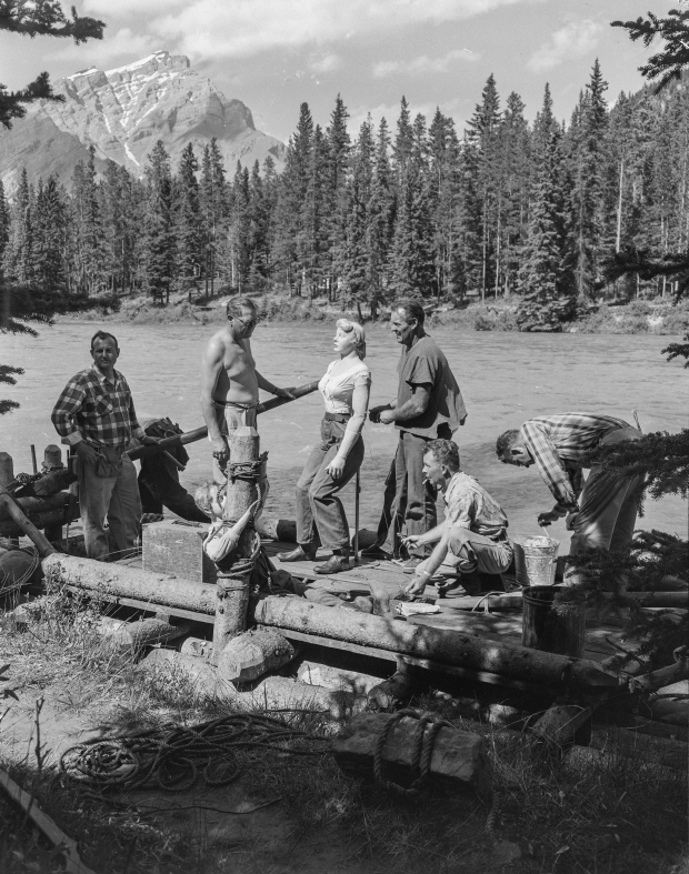"One of four wooden rafts used in the film 'River of No Return', filmed in Jasper and Banff in 1953. Notice the ""stunt double dummies"" standing in for film stars Marilyn Monroe and Robert Mitchum. (Photo Credit: Provincial Archives of Alberta PA3057.4)"