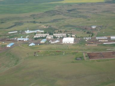 Rosebud Colony today, notice the residences and communal kitchen in the center screened by trees, and the barns and feedlots surrounding. The Rosebud River is in the background. (Photo by Simon M. Evans)