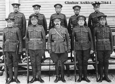 Kainai and Siksika recruits of the 191st Battalion. L-R Back Row: George Coming Singer; Joe Crow Chief; Dave Mills; George Strangling Wolf; Mike Foxhead, [Blackfoot, died overseas], 1919. L-R front row: Nick King; Harold Chief Moon; Lt. Col. Bryan; Joe Mountain Horse; Mike Mountain Horse. Glenbow Archives NA-2164-1.