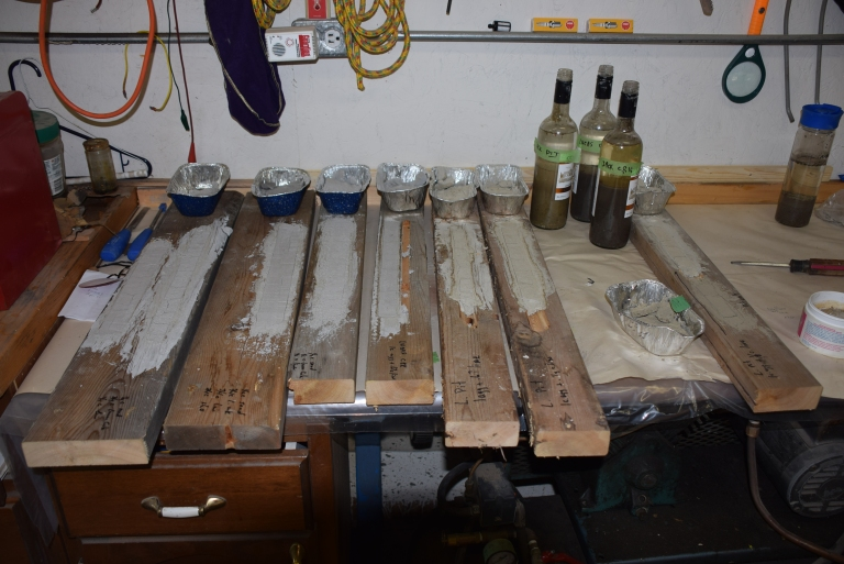 Mock-ups of daubing are tested for appearance, shrinkage and strength using various mixtures of lime hydrate with sand and clay from creeks and embankments at the ranch. The bottles at the upper right corner allow sediments to settle out to determine proportions of silt, clay, sand and organic matter and determine sand grading and colour. Sand is an important determinant of appearance in daubing and mortars. Traditional daubing is authentic, time-tested, and has physical properties that help draw moisture from the timber and contribute to long-term conservation of the logs. Source: Historic Resources Management Branch.