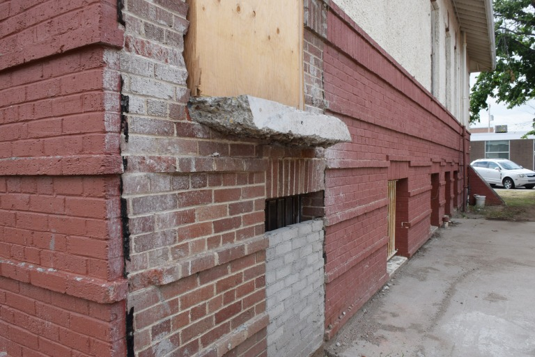 Unpainted masonry is exposed after the demolition of a large addition, previously used for the Town's emergency services, connected to the historic building's northwest corner. Areas like this are important evidence of earlier (and sometimes original) stucco colour and mortar joint profiles. Both the stucco and brick masonry exterior were painted. Source: Historic Resources Management Branch.