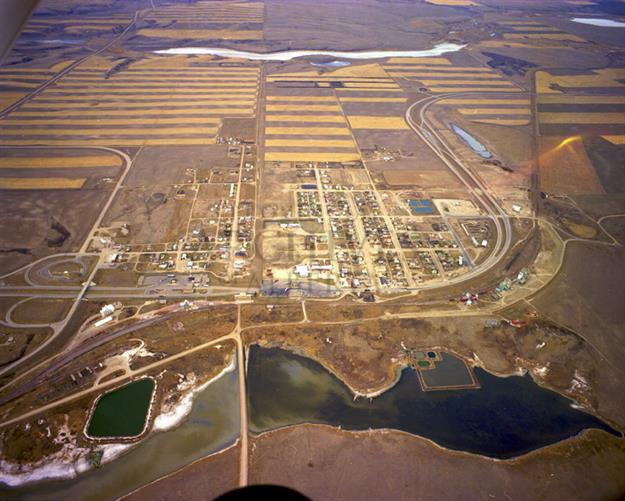 Coutts, AB and Sweet Grass, MT from the east, November 1980. The International Border is visible running through the photograph slightly to the left of centre. The United States/Montana is to the left and Canada/Alberta is to the right.  Source: Provincial Archives of Alberta, A12502