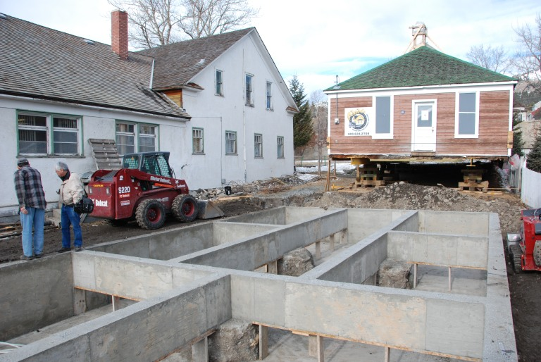 "A building needs a ""good hat and boots."" The original wood structure(s) sat directly on grade and needed a new foundation. A concrete grade beam and pile foundation was constructed in 2009 and the building was moved approximately 1 metre west for more space along the east wall, where a gap of mere inches from the neighbouring residence prevented any access for rehabilitation or maintenance. The move was limited to ensure the west side remained basically as it was in 1922.  A substantial crawl space within the foundation provides space for new heating systems and ducts."