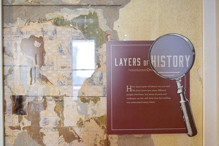 An exhibit reveals the mosaic of historic wallpaper and other finishes preserved within the drywall interior.