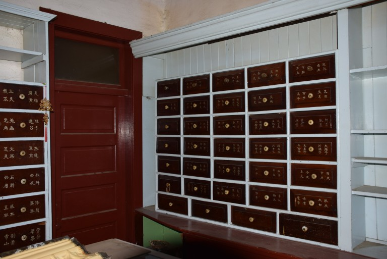 (Above) Interior photo showing main floor apothecary cabinets. Source: Historic Resources Management Branch, 2014. (Below) Chinese medicines stores in apothecary cabinets. Source: Historic Resources Management Branch, 2014.